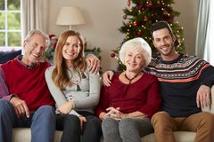 Portrait Of Senior Parents With Adult Offspring Wearing Festive Jumpers Sitting On Sofa In Lounge At Home On Christmas Day royalty free stock photos