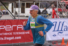 Portrait of senior participant hurrying to finish line during `Dnepr Eco Marathon` race. DNEPR, UKRAINE - SEPTEMBER 25, 2016:Portrait of senior participant royalty free stock photography
