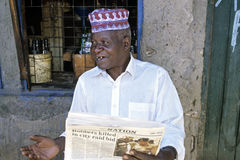 Portrait senior reading old newspaper for liquor store Royalty Free Stock Photo