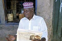 Portrait senior reading old newspaper for liquor store. Kenya, capital, city Nairobi, neighborhood Sinai Village: everyday living in a slum, an elderly man sits royalty free stock photo