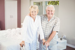 Portrait of senior smiling couple with walker. At home stock photography