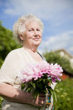 Portrait of senior smiling woman with flowers Royalty Free Stock Photography