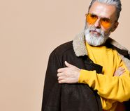 Senior stylish rich man with a beard and mustache in a leather coat stock photo