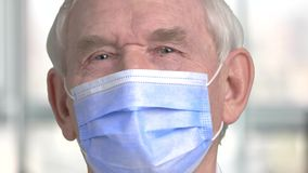 Portrait of senior surgery doctor. Close up face of old male doctor with blue mask stock video footage
