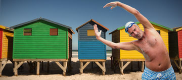 Composite image of portrait of senior swimmer exercising. Portrait of senior swimmer exercising against colorful huts on sand at beach Royalty Free Stock Photography