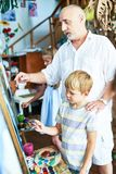 Art  Teacher Helping Children. Portrait of senior teacher helping little boy painting picture in art studio standing by easel with other children in background Stock Images