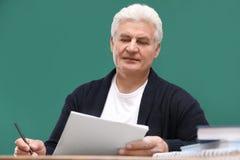Portrait of senior teacher at table. Against green chalkboard stock photo