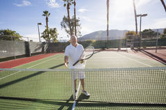 Portrait of senior tennis player offering handshake on court Royalty Free Stock Photography