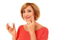 Portrait of senior woman applying anti-aging cream onto face, isolated. On white Royalty Free Stock Photos