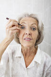 Portrait of senior woman applying eyeliner in bathroom Royalty Free Stock Photos