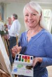 Portrait Of Senior Woman Attending Painting Class With Teacher          In Background royalty free stock photography
