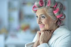 Portrait of senior woman in bathrobe with curlers. Close up portrait of senior woman in bathrobe with curlers royalty free stock photography