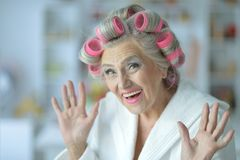 Portrait of senior woman in bathrobe with curlers. Close up portrait of senior woman in bathrobe with curlers royalty free stock images