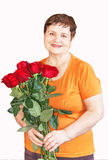 Portrait of senior woman with bouquet (bunch) of red roses. Royalty Free Stock Photos