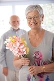 Portrait of senior woman with bouquet smiling Royalty Free Stock Photo