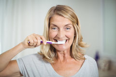 Portrait of senior woman brushing her teeth in bathroom royalty free stock photography