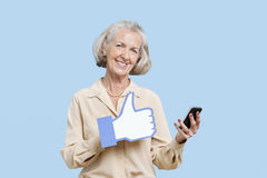 Portrait of senior woman with cell phone holding fake like button against blue background Stock Photos