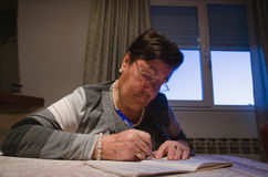 Portrait of senior woman with crossword puzzle Stock Images