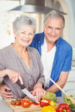 Portrait of senior woman cutting while man embracing in kitchen Stock Images