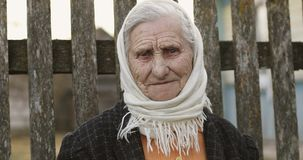 Portrait of a senior woman with deep wrinkles in a scarf on the background of an old fence. Sad grandmother looks to the camera stock footage