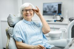 Portrait of a senior woman at the dental office. Portrait of a beautiful senior woman with healthy smile sitting at the dental office stock photos