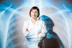 Doctor on the x-ray of human lungs background. Portrait of a senior woman doctor in uniform with projected x-ray of human lungs Stock Photography