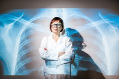 Doctor on the x-ray of human lungs background. Portrait of a senior woman doctor in uniform with projected x-ray of human lungs Stock Image