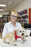 Portrait of senior woman with dog in pet shop Royalty Free Stock Photos