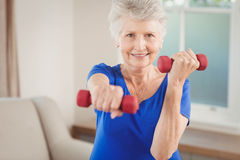 Portrait of senior woman exercising with dumbbells royalty free stock images