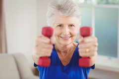 Portrait of senior woman exercising with dumbbells royalty free stock photo