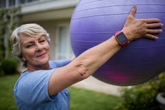 Portrait of senior woman exercising with fitness ball Stock Images