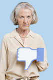 Portrait of senior woman with fake dislike button against blue background Royalty Free Stock Photo