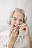 Portrait of senior woman flossing teeth in bathroom Stock Photo