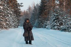 Portrait of senior woman fur coat and hat standing in cold winter snow covered forest, telephoto Royalty Free Stock Photo