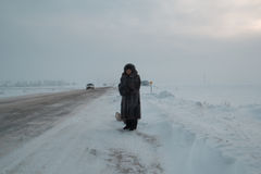 Portrait of senior woman fur coat and hat standing at winter snow covered field road, telephoto Stock Images