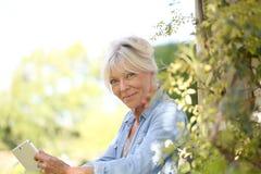 Portrait of senior woman in garden using tablet. Senior woman in garden using tablet Royalty Free Stock Photos