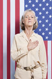 Portrait of senior woman with hand over heart against American flag Stock Photos