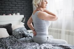 Senior woman having back pain sitting on bed. Portrait of senior woman having back pain sitting on bed Stock Photo