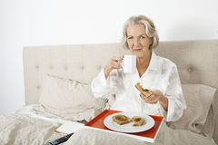 Portrait of senior woman having breakfast in bed Royalty Free Stock Photos