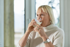 Portrait of senior woman having breakfast. Portrait of senior caucasian woman drinking fresh milk for breakfast at home Royalty Free Stock Photography