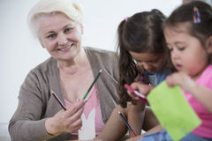 Portrait of senior woman helping granddaughters in making handicrafts at home Stock Image