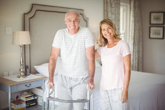 Portrait of senior woman helping man to walk with walker Royalty Free Stock Photos