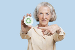 Portrait of senior woman holding badge with recycling symbol against blue background Royalty Free Stock Photos