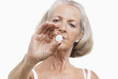 Portrait of senior woman holding a pill against white background Stock Photo