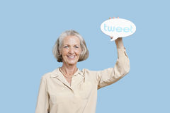 Portrait of senior woman holding tweet bubble against blue background Stock Images