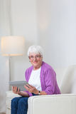 Portrait of a senior woman at home using a tablet computer Stock Photos