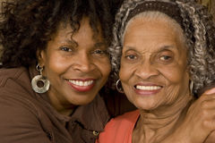 Portrait of a senior woman hugging her daughter. Mature African American mother hugging her daughter Stock Photos
