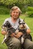 Portrait. Senior woman hugs her two pets, black and silver miniature schnauzer dog in countryside Stock Image