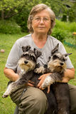 Portrait. Senior woman hugs her two pets, black and silver miniature schnauzer dog in countryside Royalty Free Stock Photos