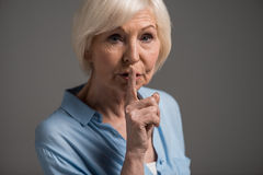 Portrait of senior woman with hush gesture Stock Image